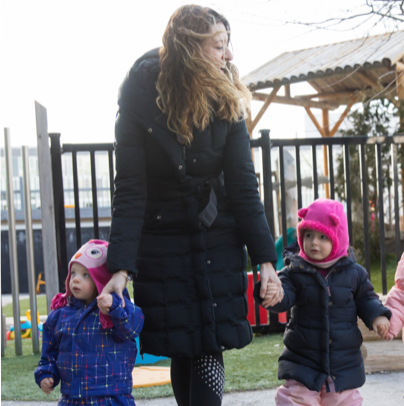 Young students and educator at JCC Daycare and Preschool holding hands outside